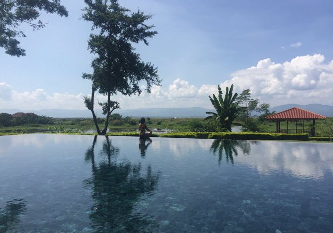 Sanctum Inle Resort's serene pool overlooks the banks of the storied Inle Lake and surrounding hills.
